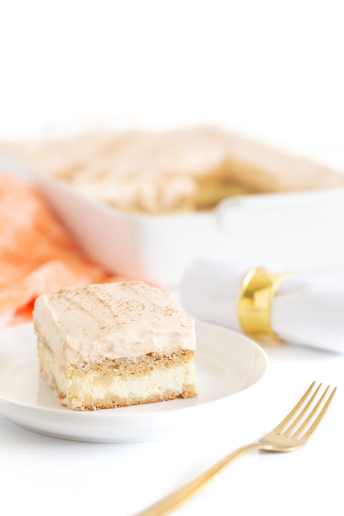 slice of pumpkin layer cake on a small white plate with a lip, gold fork and cloth napkin roll with gold napkin ring. Baking dish in the background.