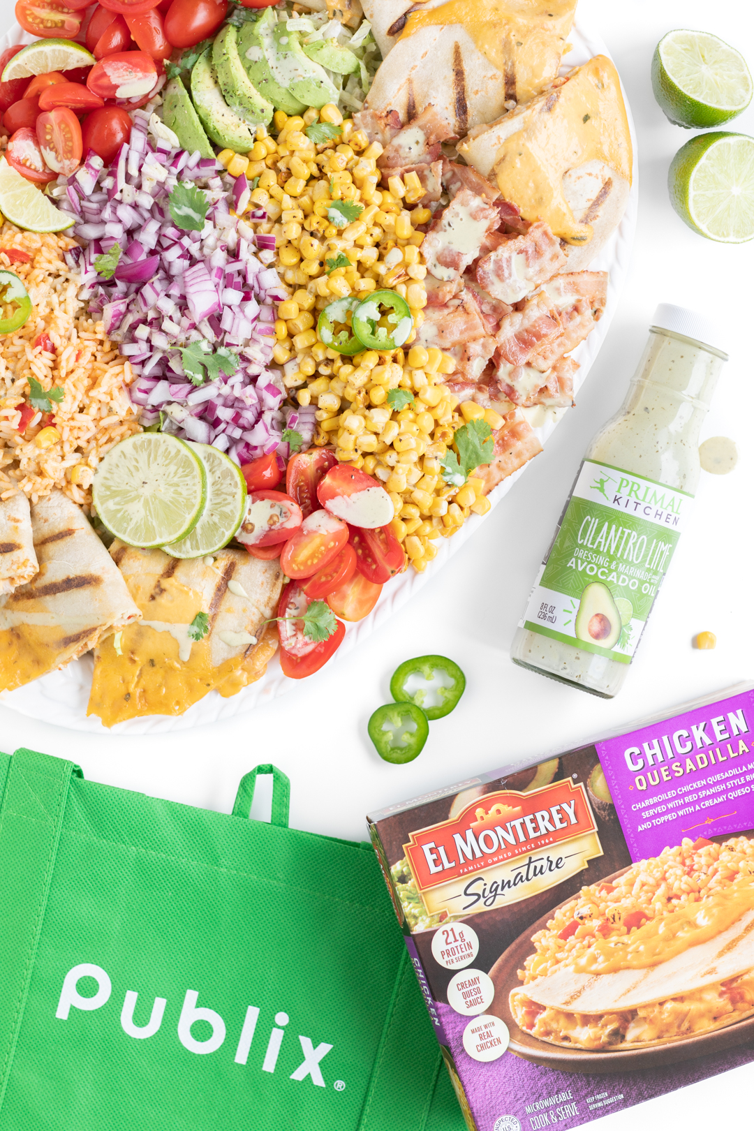 Over the top photo of large family salad, reusable publix shopping bag, el monterey quesadilla meal and primal kitchen lime and cilantro dressing