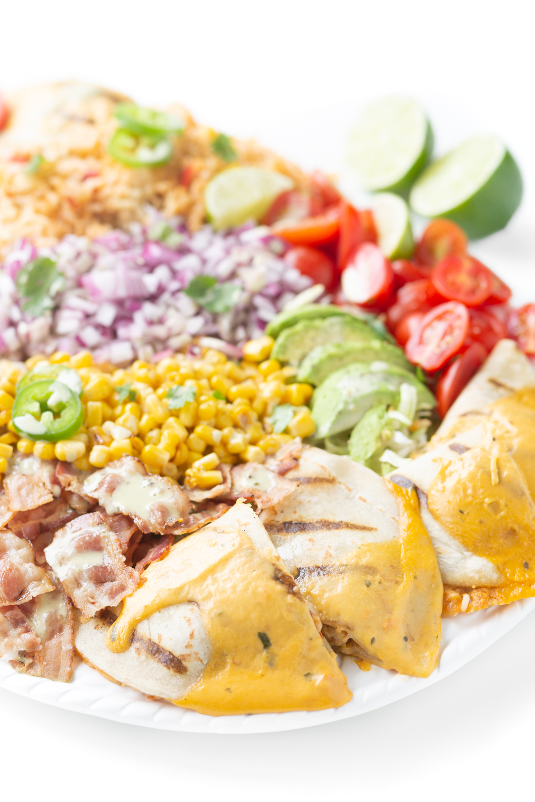 mexican inspired salad tray with mexican rice, quesadillas with cheesy sauce, bacon, grape tomatoes, fresh avocado slices, diced onions