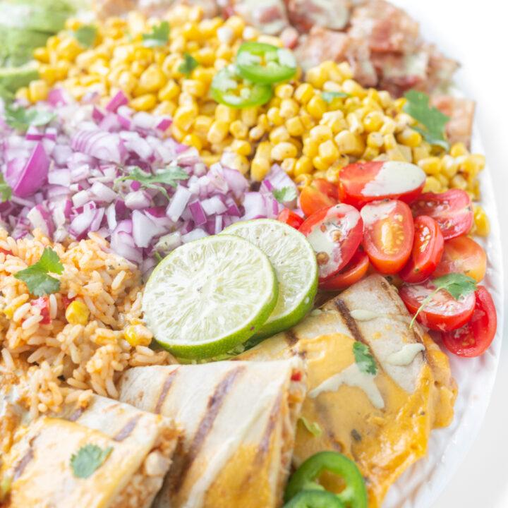 quesadilla salad with chicken quesadilla wedges, lime slices, mexican rice, grape tomatoes, corn, bacon, cilantro
