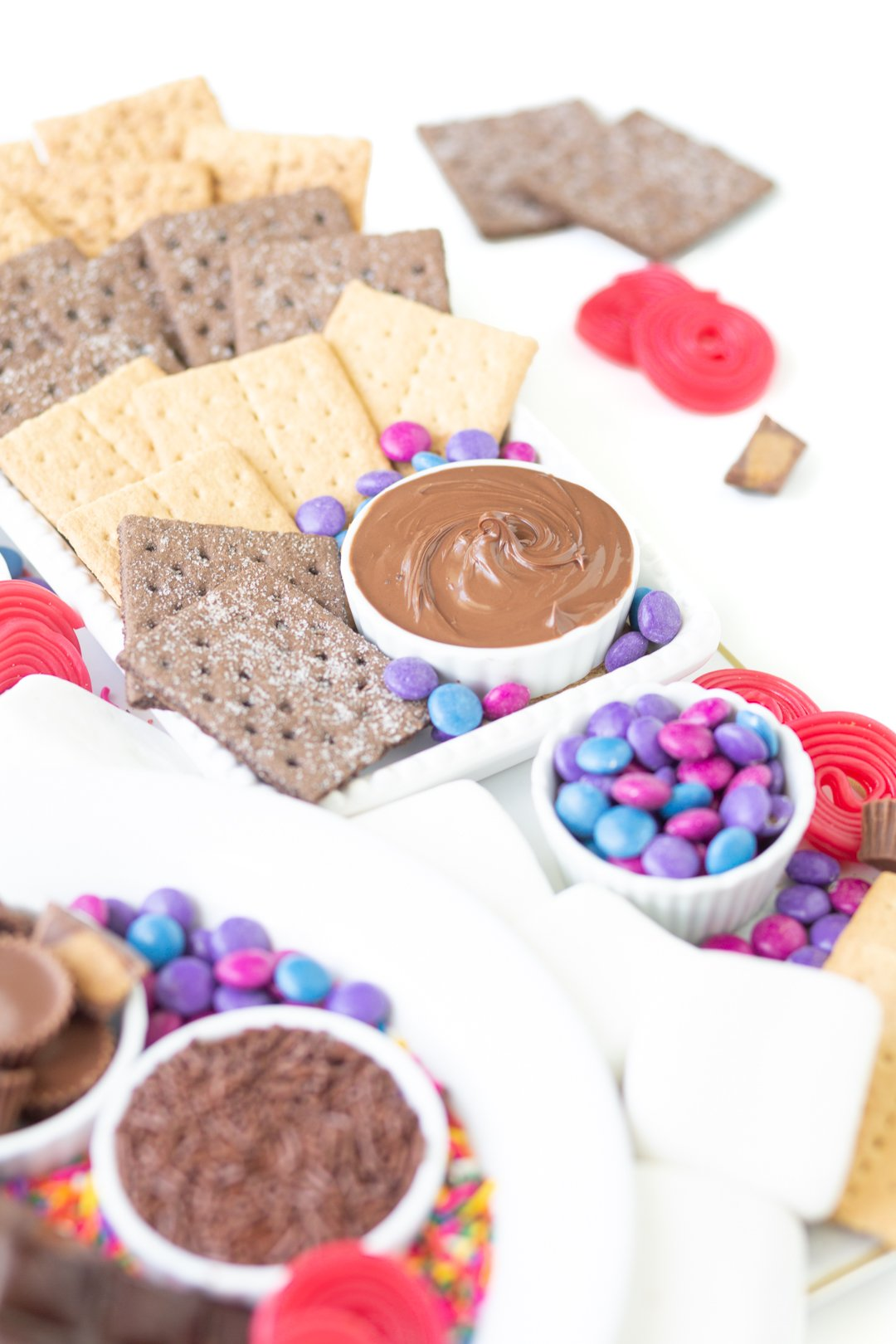 s'mores dessert grazing board with candies, spreads, graham crackers