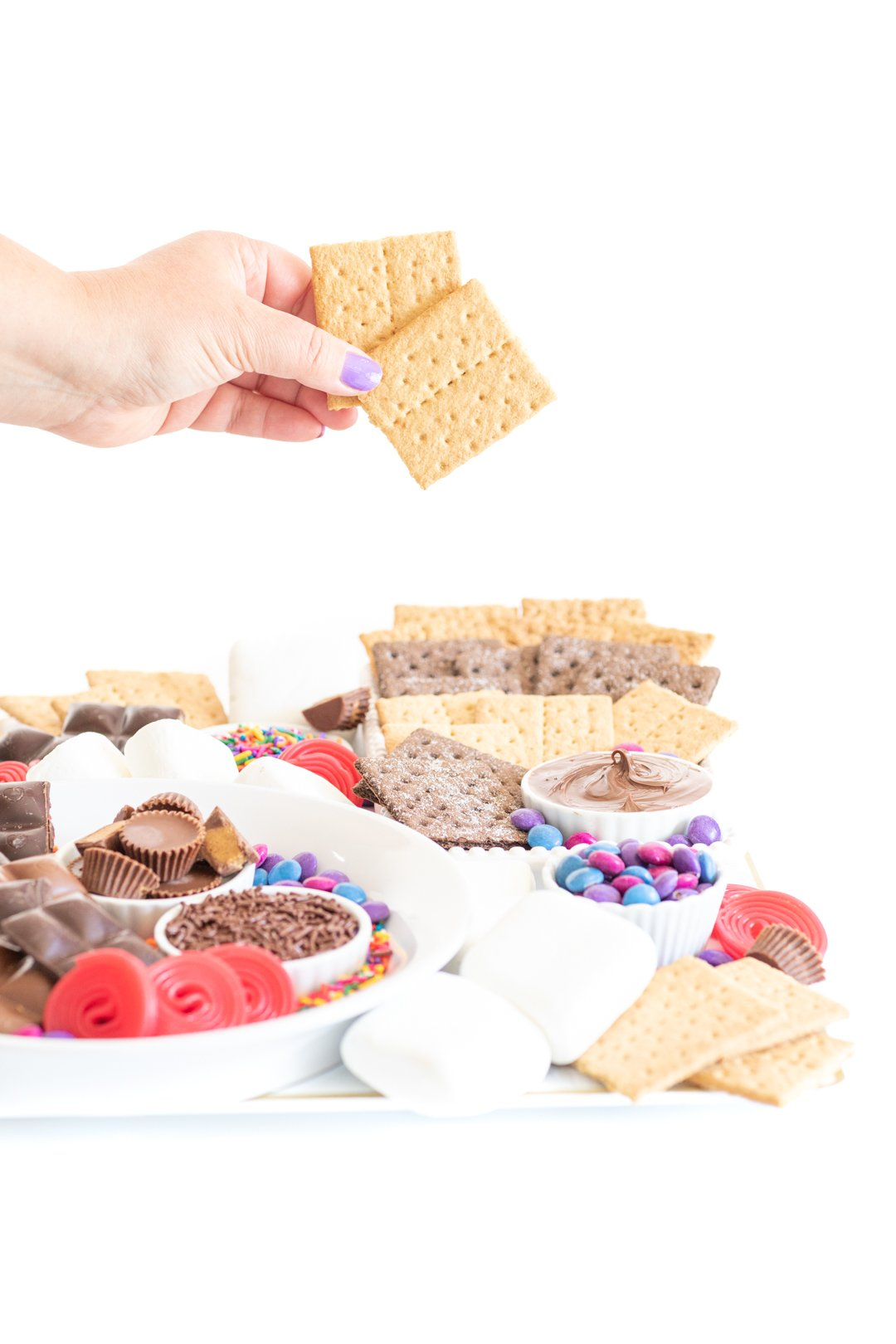 setting up a s'mores dessert board with graham crackers, candies and chocolate