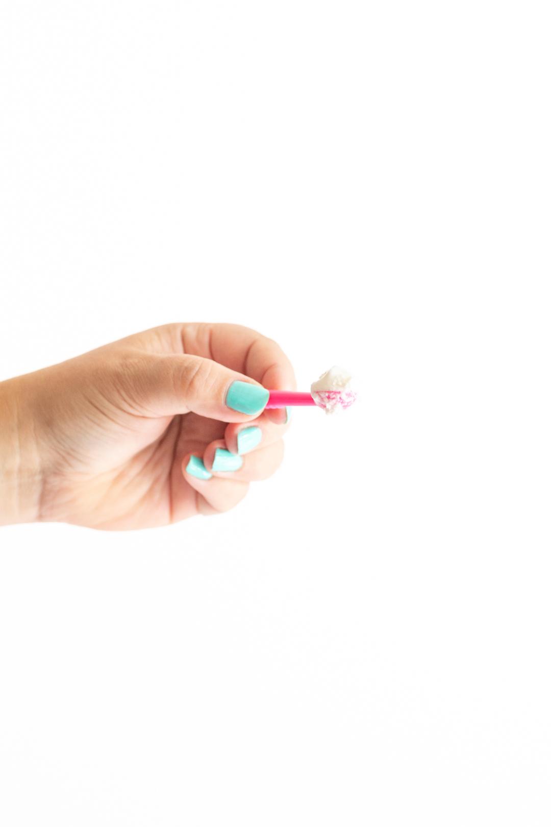 tiny pink ice cream scoop with tiny scoop of vanilla ice cream on top