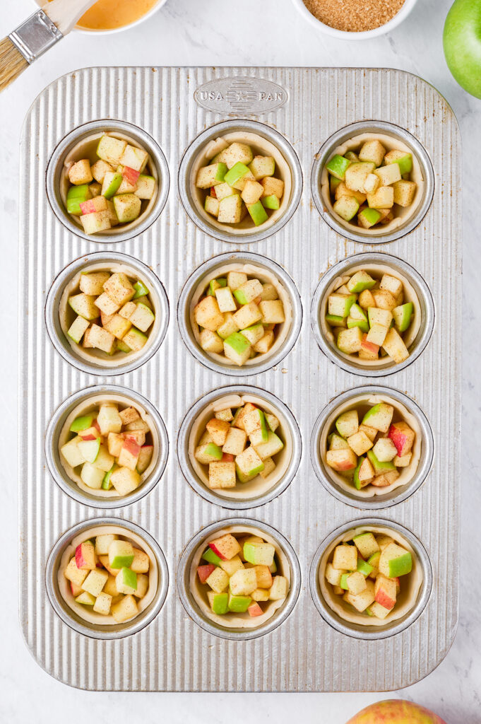 preparing mini apple pies in a muffin tin, chopped apples placed on top of dough circles