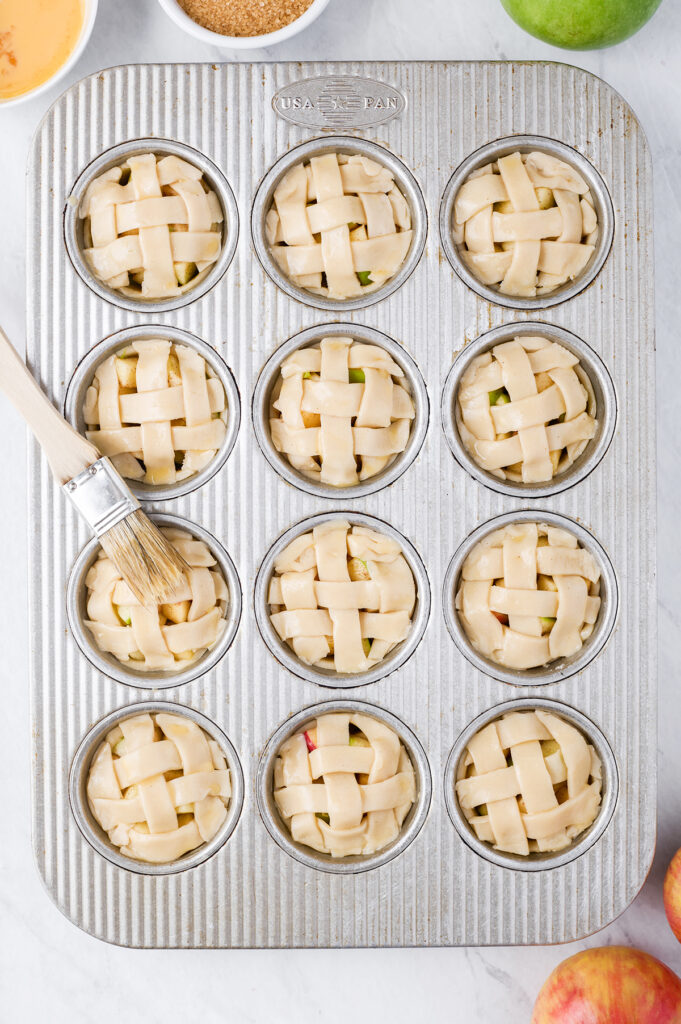 brushing on egg wash over mini pies in a muffin tin
