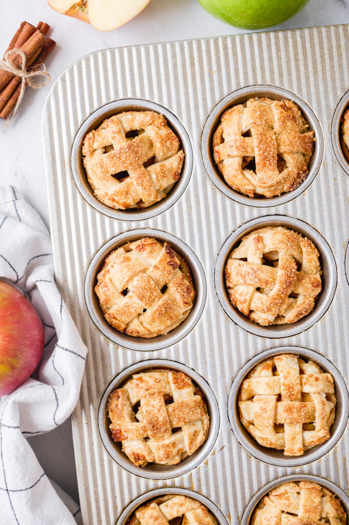 close up of individual apple pies baked in a muffin tin with fresh apples surrounding it