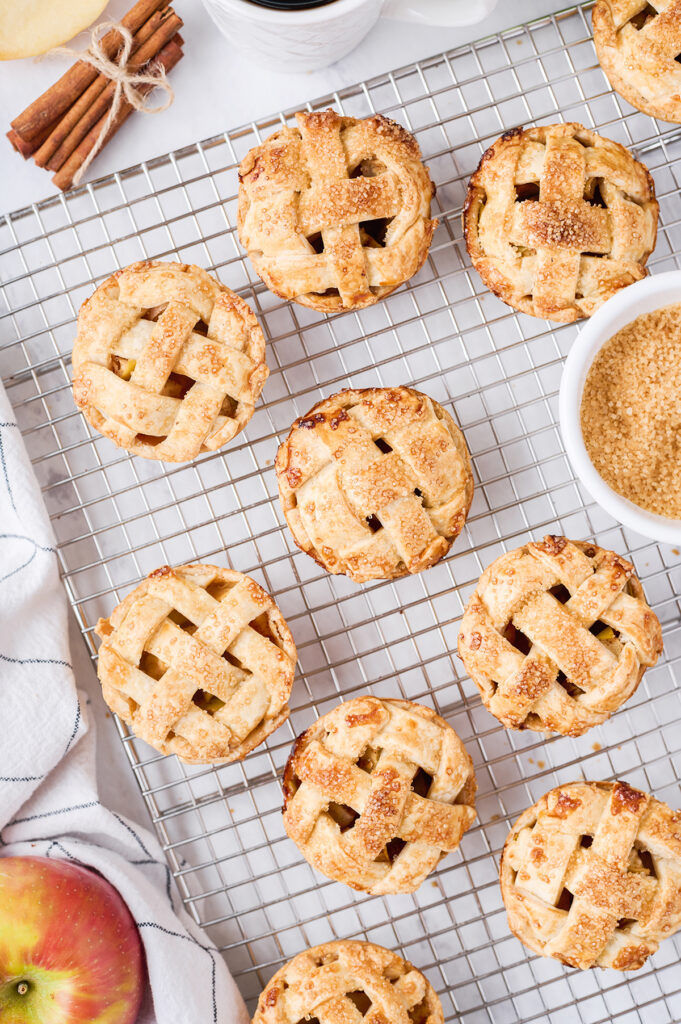 little apple pies set out on a cooking rack with sugar and cinnamon in bowl next to it