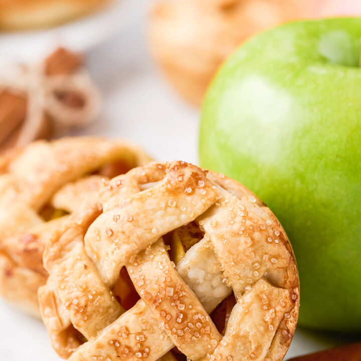 pretty little apple pies resting against a green apple