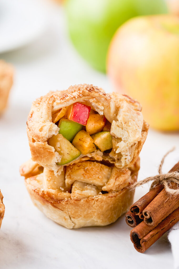 two mini apple pies stacked on top of each other. the top pie has a bite taken out of it to reveal the pretty red and green apple chunks inside