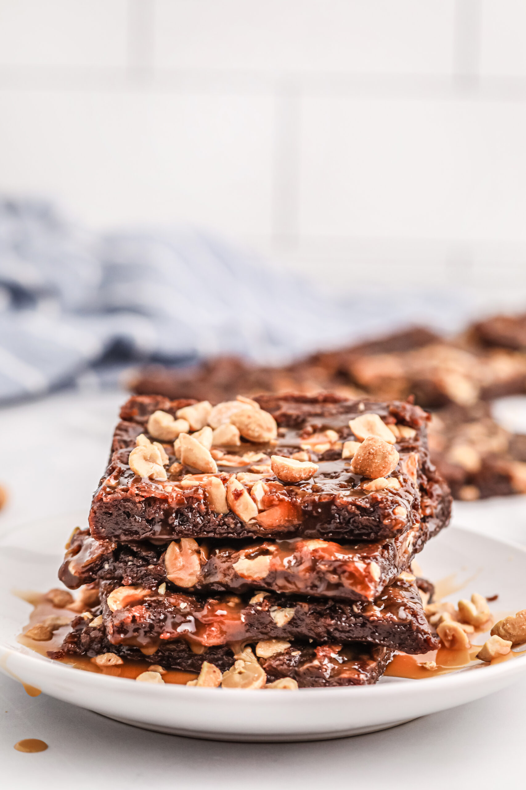stack of thin, peanut topped brownies on a plate