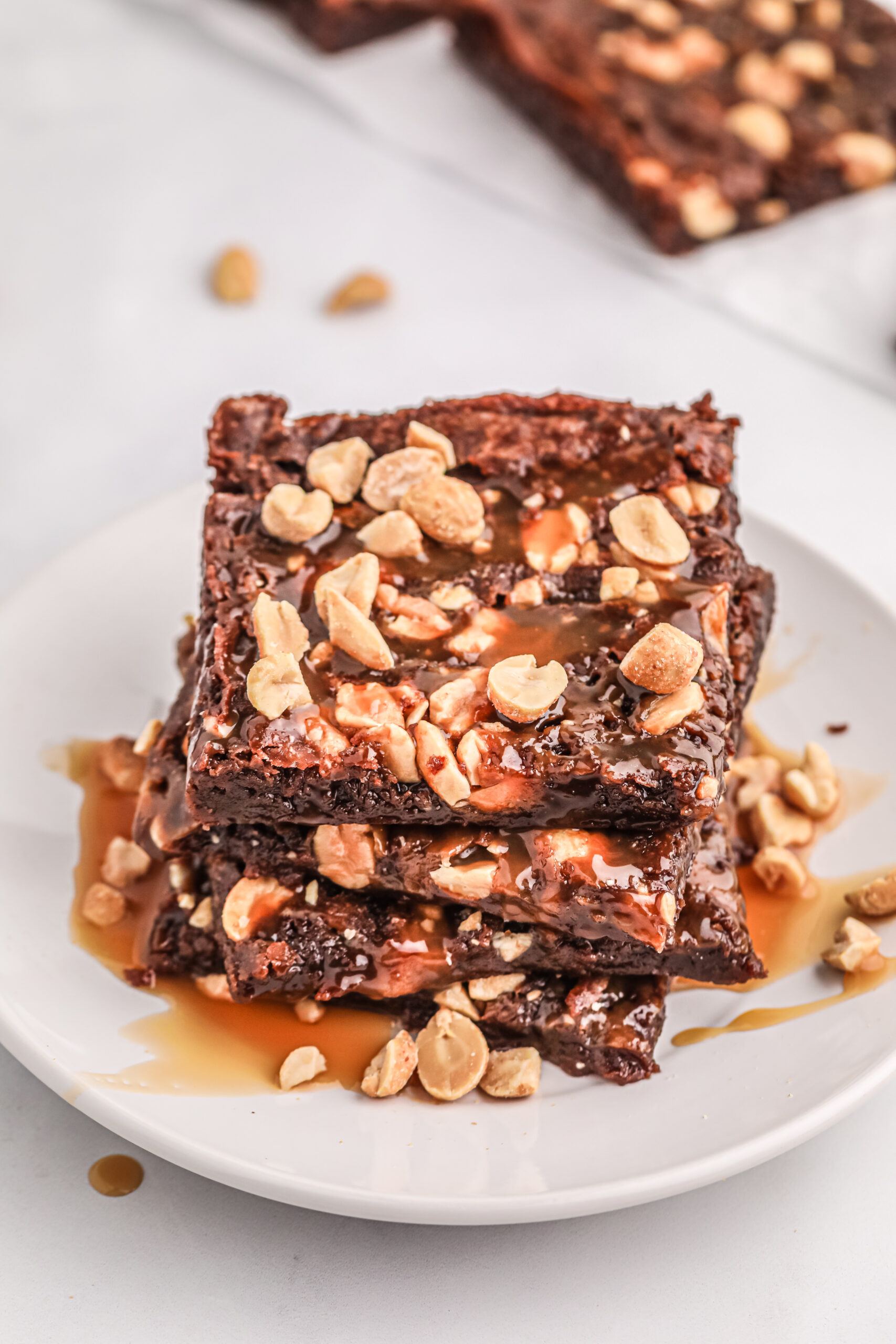 up close downward view of thin snickers brownies on a small white plate.