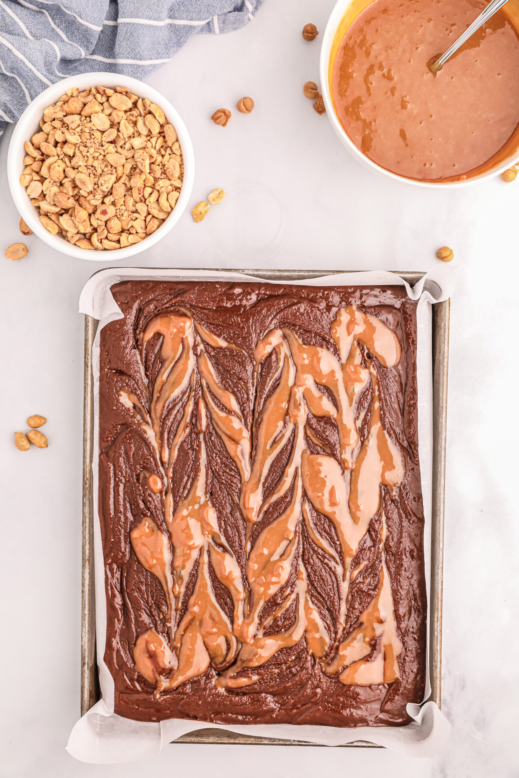 melted caramel bits swirled into brownie mixture in a baking sheet