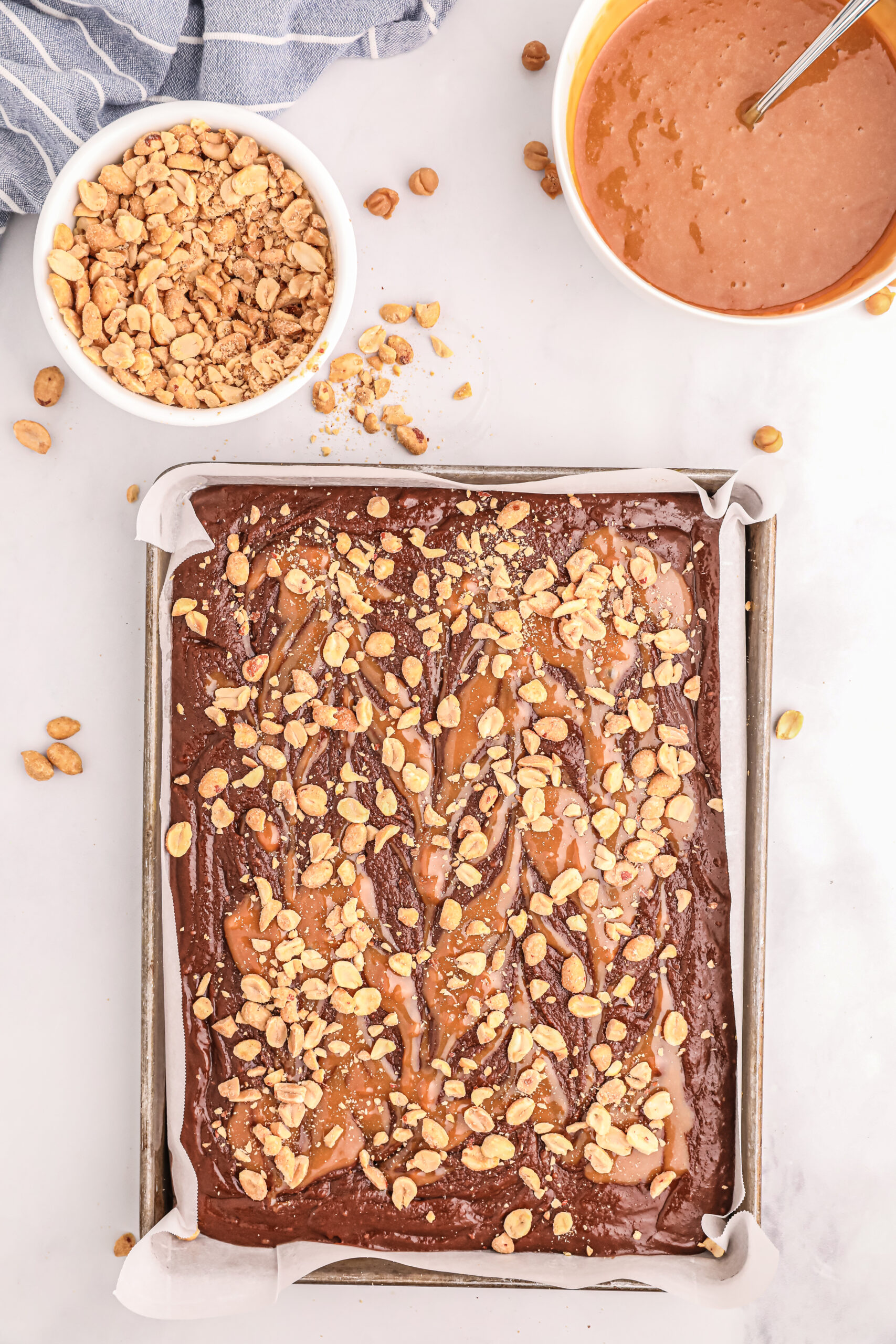 caramel swirl and peanuts topping a brownie batter in a sheet pan