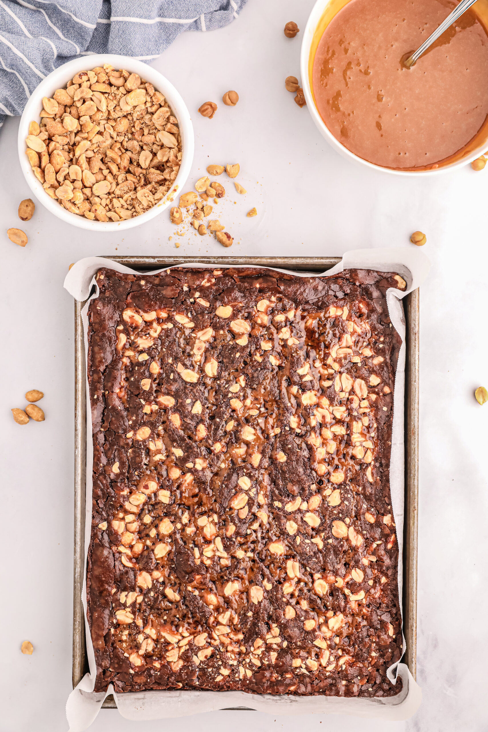 freshly baked snickers brownies on a baking sheet