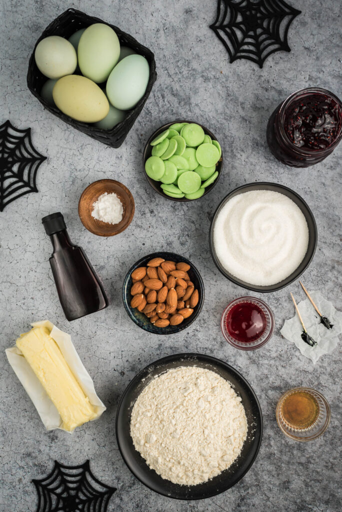 halloween witch cookie ingredient flat lay including black food coloring, butter, sugar, almonds