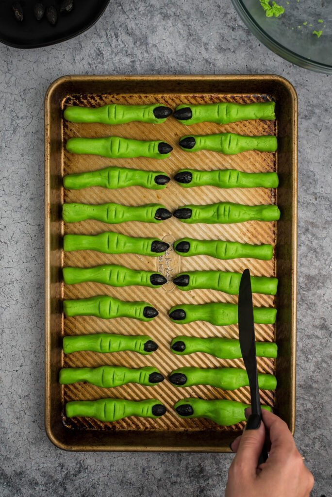 Green witch cookies with black fingernails on a baking sheet. Woman's hand holding a black plastic knife to show how to make indents into the cookies to make them look like fingers