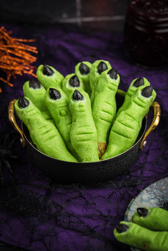 up close of witch finger cookies. green finger like cookies with black almond fingernails