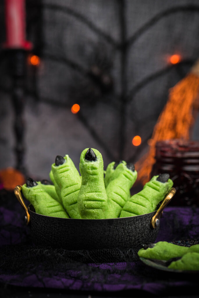 black cauldron filled with witch finger cookies in a halloween party setting