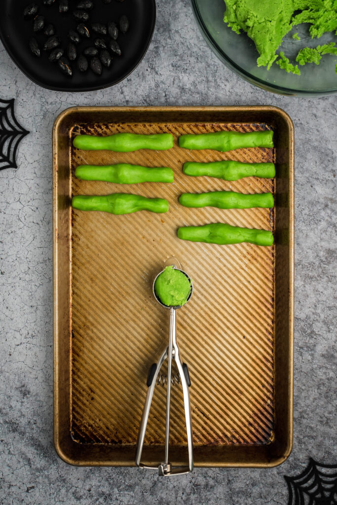 measuring out green sugar cookie dough to prepare witch finger cookies