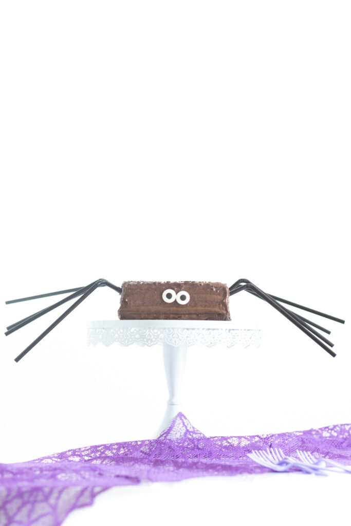 funny halloween spider cake with black straws for legs and large candy eyes
