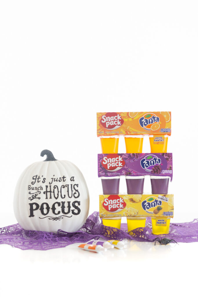 "fanta gelatin cup packs. orange, pineapple and grape next to a ceramic decorative white pumpkin that reads ""hocus pocus"""