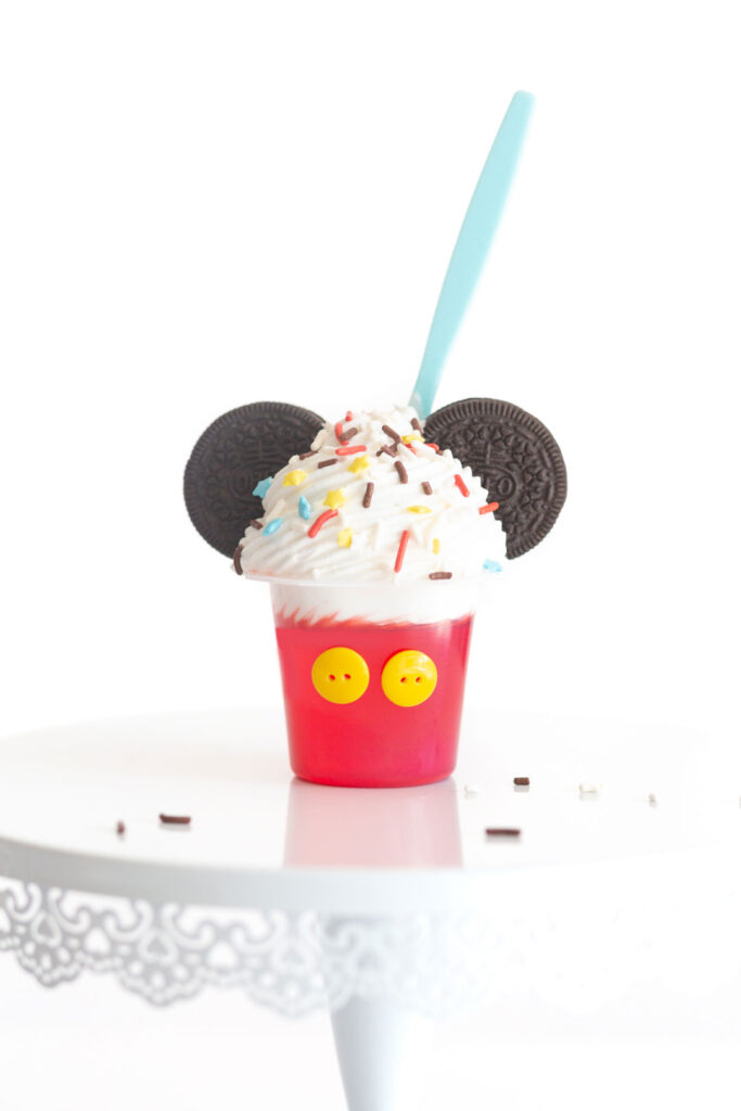 Mickey mouse jello cup decorated with yellow buttons, oreos, whipped cream and mickey mouse colored sprinkles