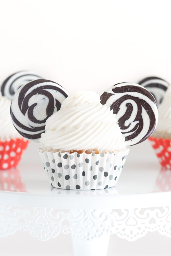 up close view of mickey mouse cupcake with vanilla buttercream, lollipops for ears and black polkadot cupcake liners