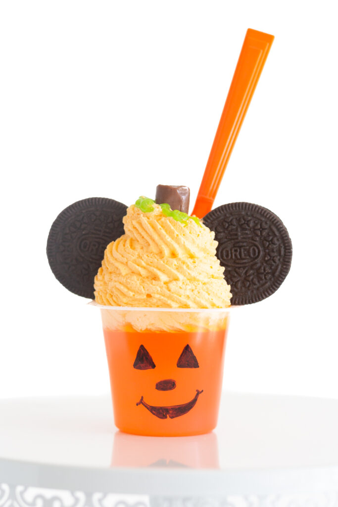 up close orange gelatin decorated like a mickey mouse pumpkin with tootsie roll stem, orange whipped topping, oreo cookies.