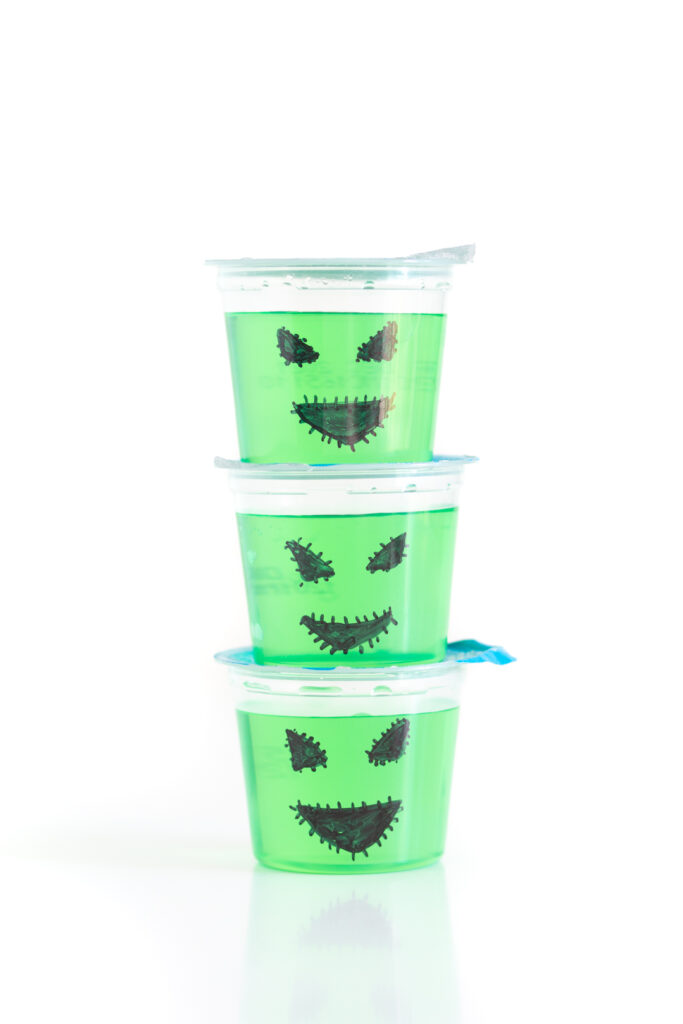 stack of three green gelatin cups, decorated for halloween