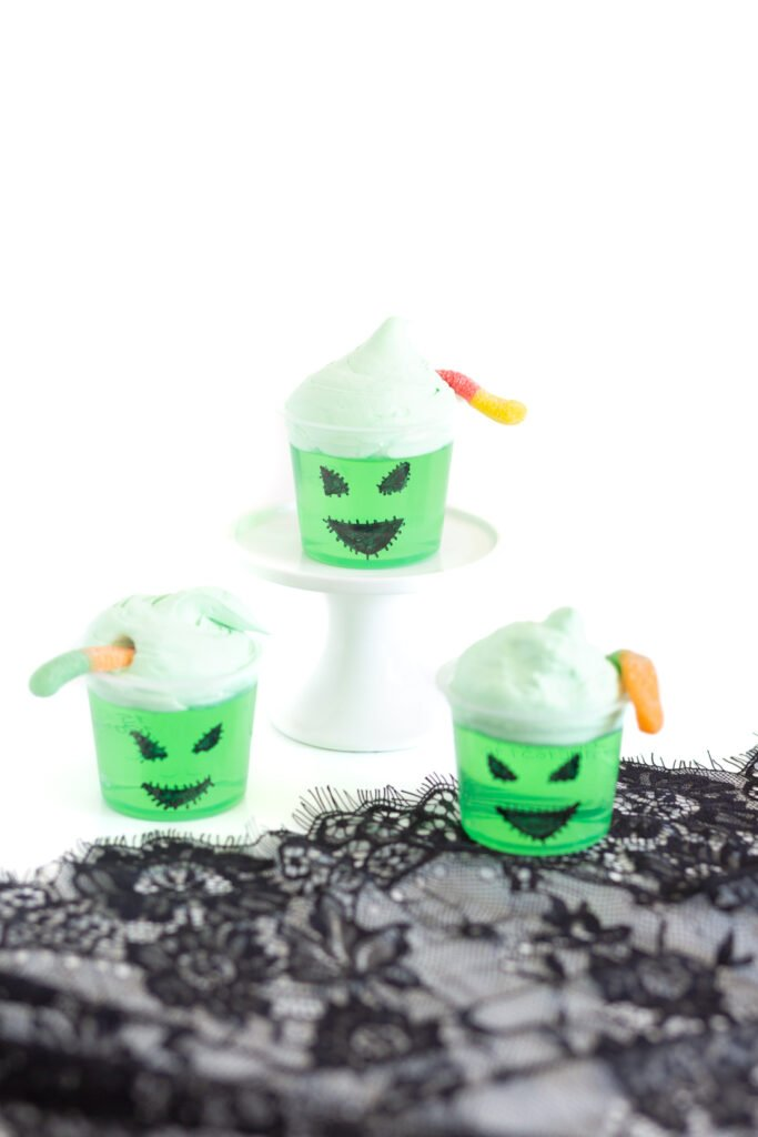 Oogie boogie jello cups using green jello, black sharpie to draw face on, green tinted cool whip and sour worms to decorate