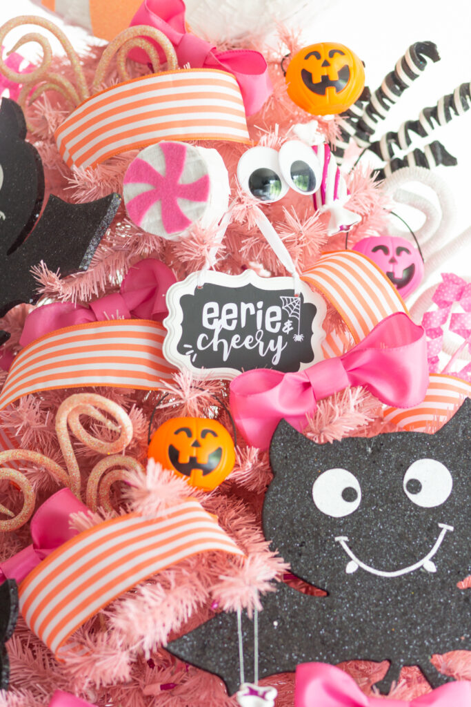 Full halloween tree decorated with pretty striped ribbons, mini pinatas, big pink bows.