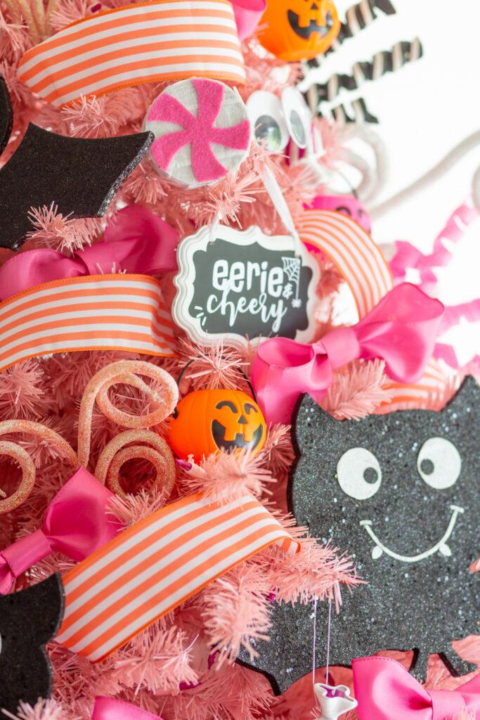 close up view of pink christmas tree with mini pumpkin treat bucket ornaments, giant bat ornaments, pink bow, mini pinatas