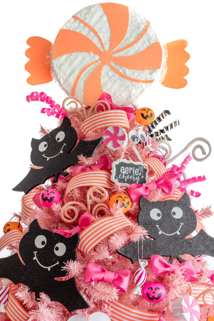 pretty pink christmas tree with pink, orange and black and white ornaments.