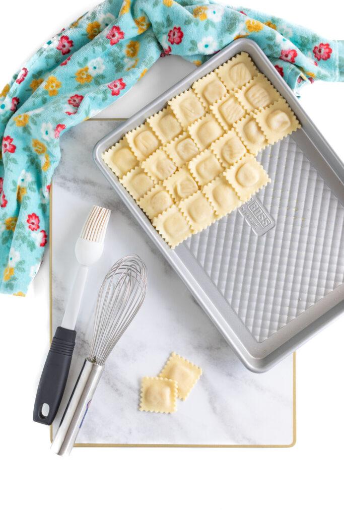 layering small cheese ravioli onto a half baking sheet to make pizza