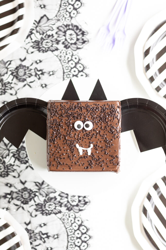square chocolate cake transformed into a bat cake with paper plate bat wings and ears and large candy eyes and icing fangs.