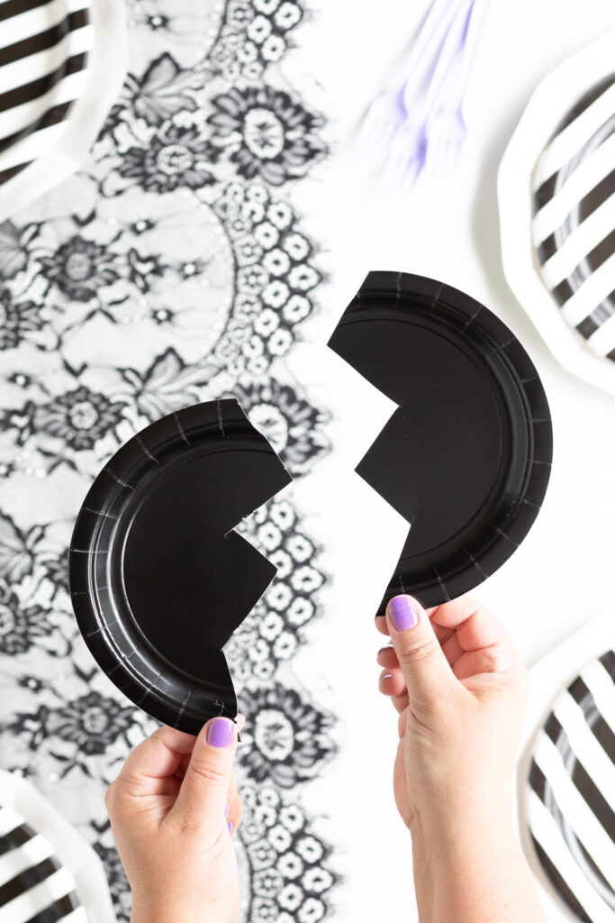 bat wings craft cut out of a small black paper plate. each wing is being held by a woman's hands