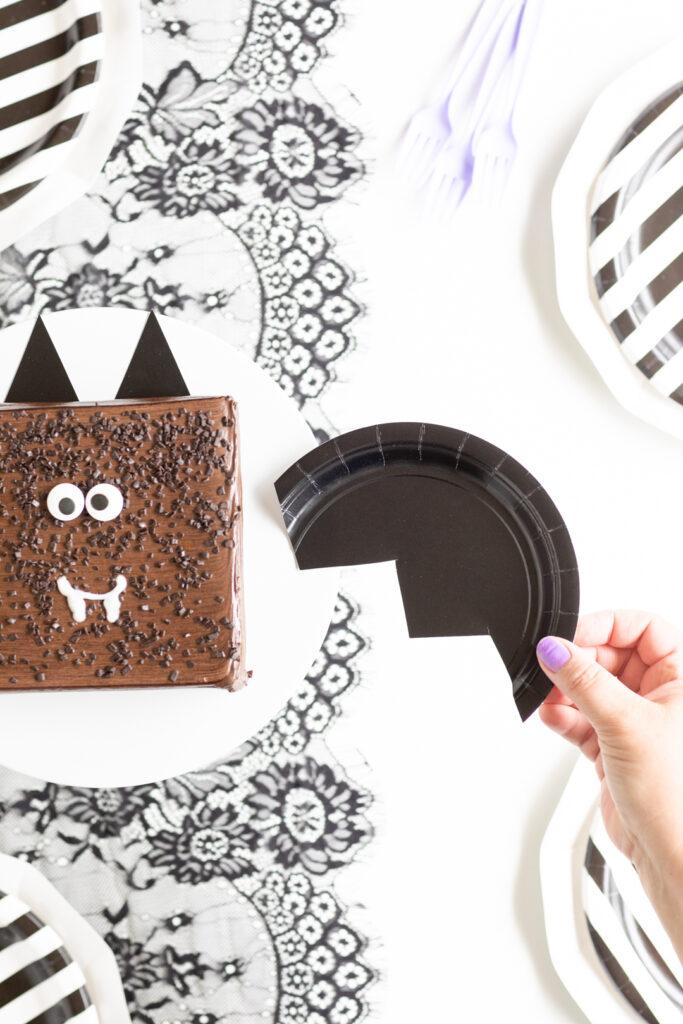 placing a craft bag wing onto a bat themed cake