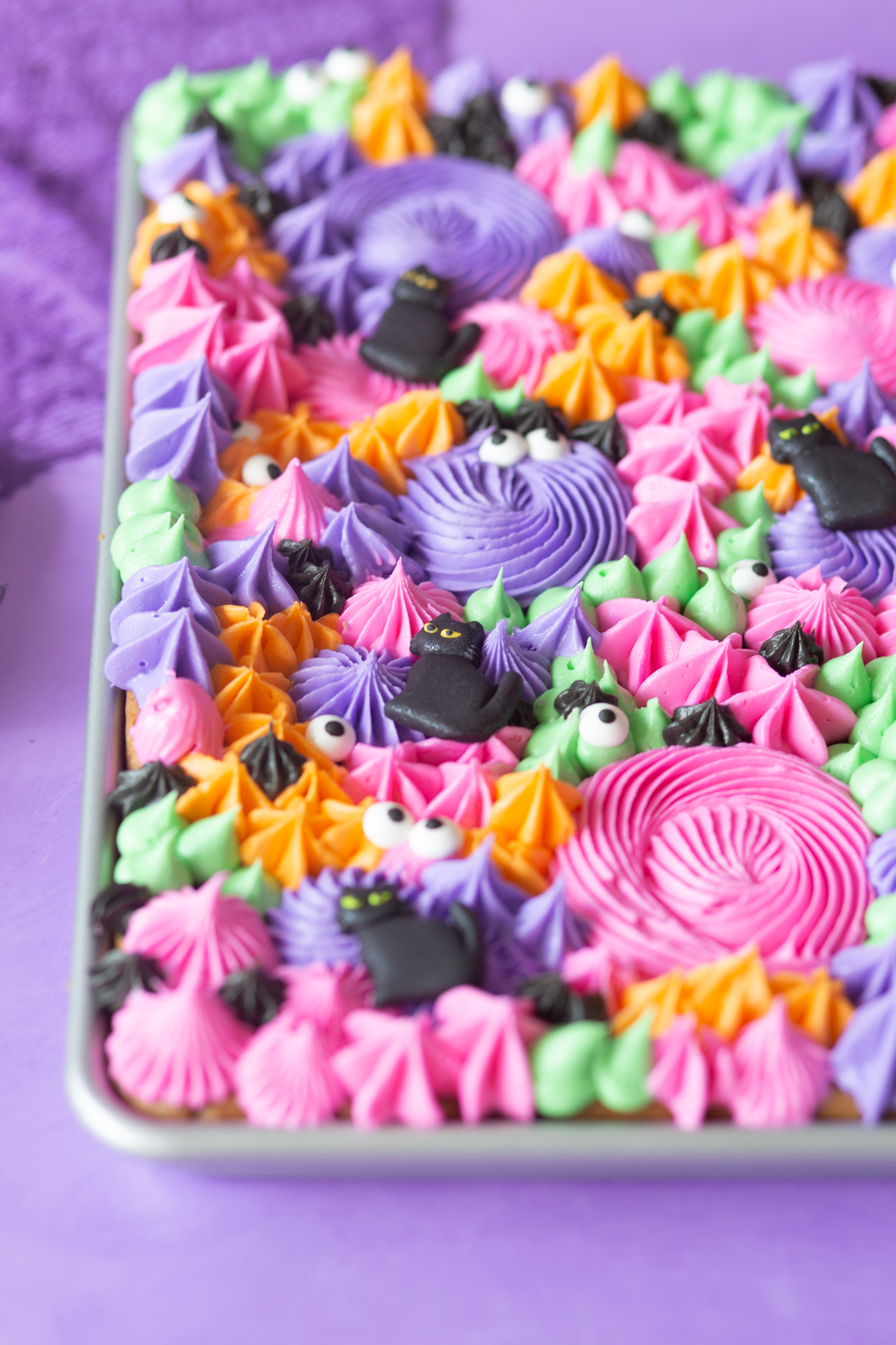 close up view of sheet pan cookies loaded with colorful buttercream frosting using different piping tips