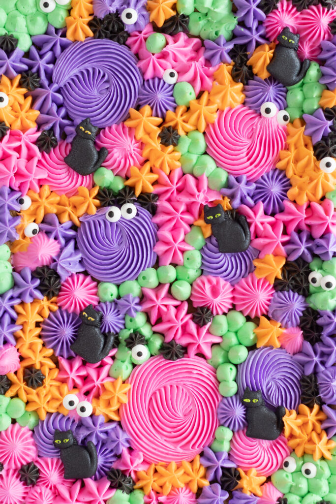 cropped in view of only frosting decorations from on top of a sheet pan cake. Cat icing decorations, small candy eyes.