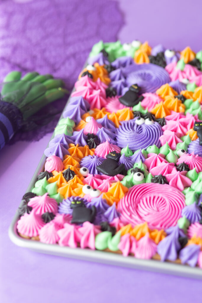 angled shot of buttercream cookie sheet with pink, green, orange, purple and black. Witch hand prop next to it.