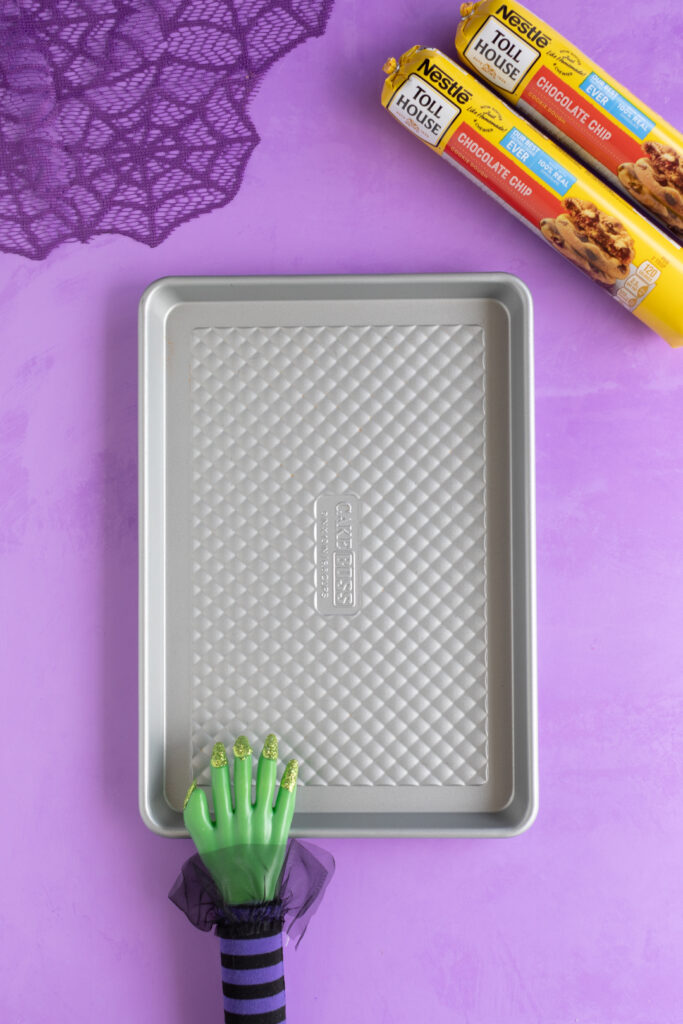 half sheet pan and two rolls of nestle cookie dough rollls on a purple backdrop. Purple web table runner in the corner. Witch hand prop resting on the sheet pan.