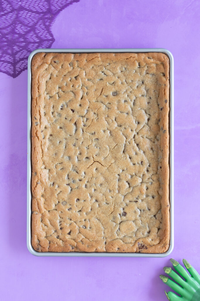 baked cookie dough on a half baking sheet on a purple backdrop. Purple web decoration in top left corner. Witch hand in bottom right corner.