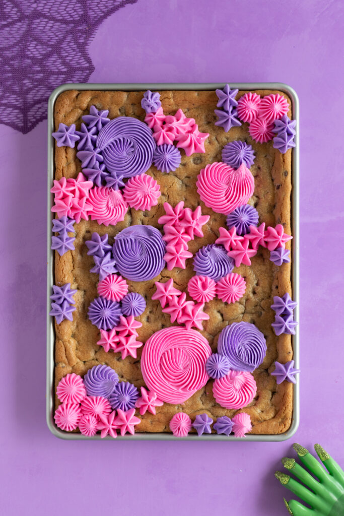 beginning stages of frosting a sheet pan cookie using pink and purple buttercream decorations using a french tip and open star tip.