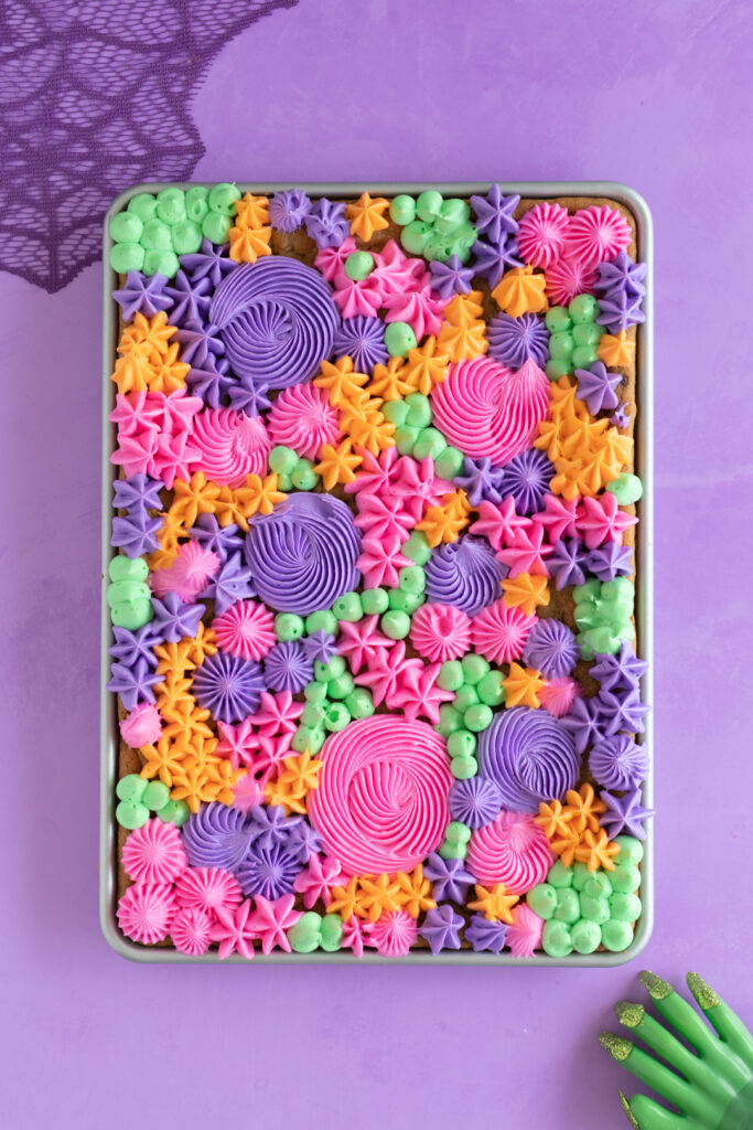 orange, purple, pink and green buttercream decorations on a half sheet pan of cookie bars